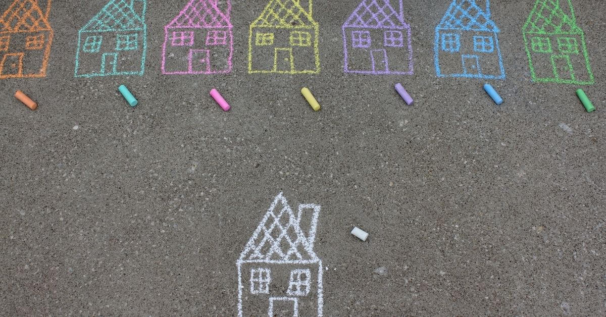 different coloured chalk drawings of houses on concrete pavement