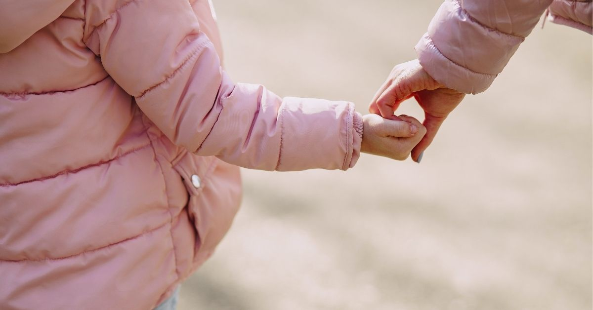 a young girl wearing a pink jacket holds her mother's hand as they walk
