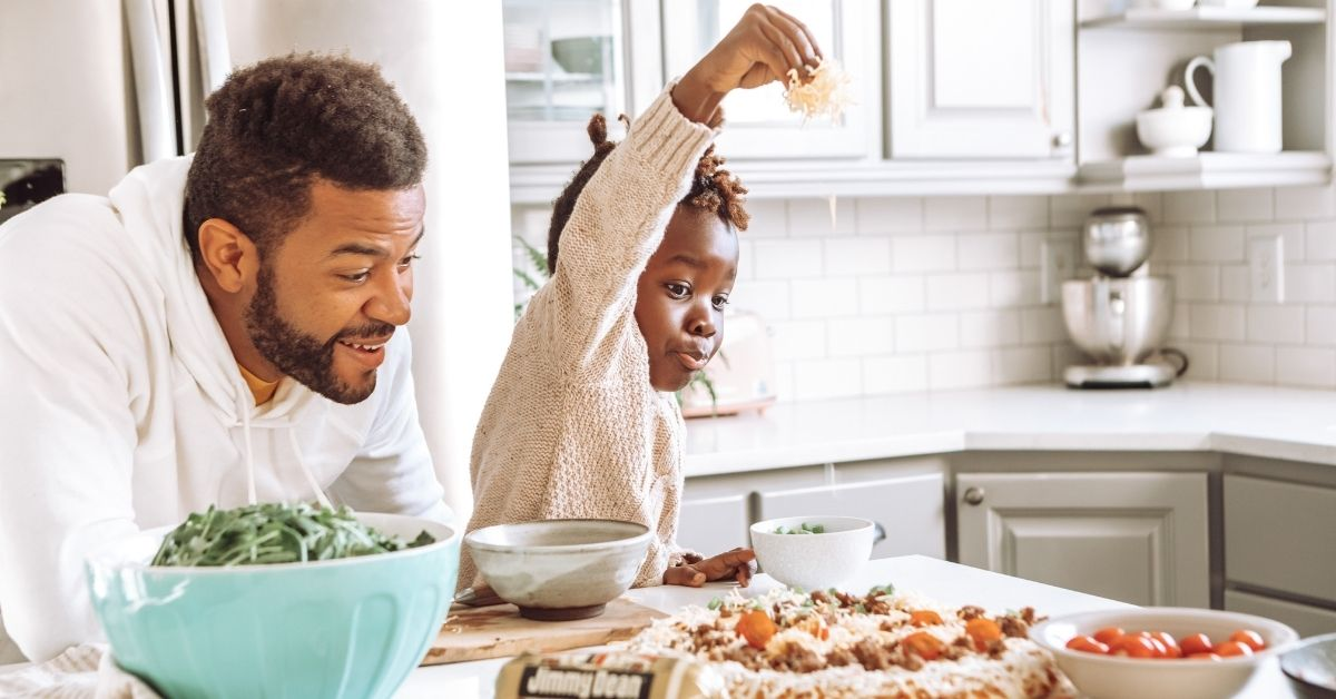 a father and child making home made pizza together