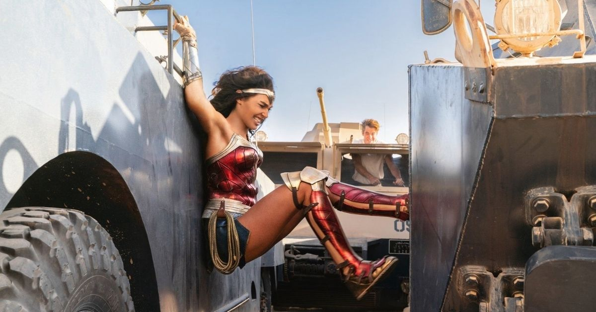 an action shot of wonder woman wedged between two moving trucks pushing with her legs